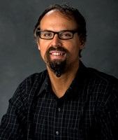 man in dark shirt against grey background