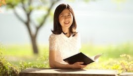 woman smiles and holds a book on brightly lit bench