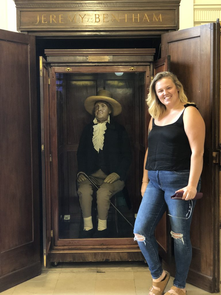 Woman with blonde hair next to a display of a man
