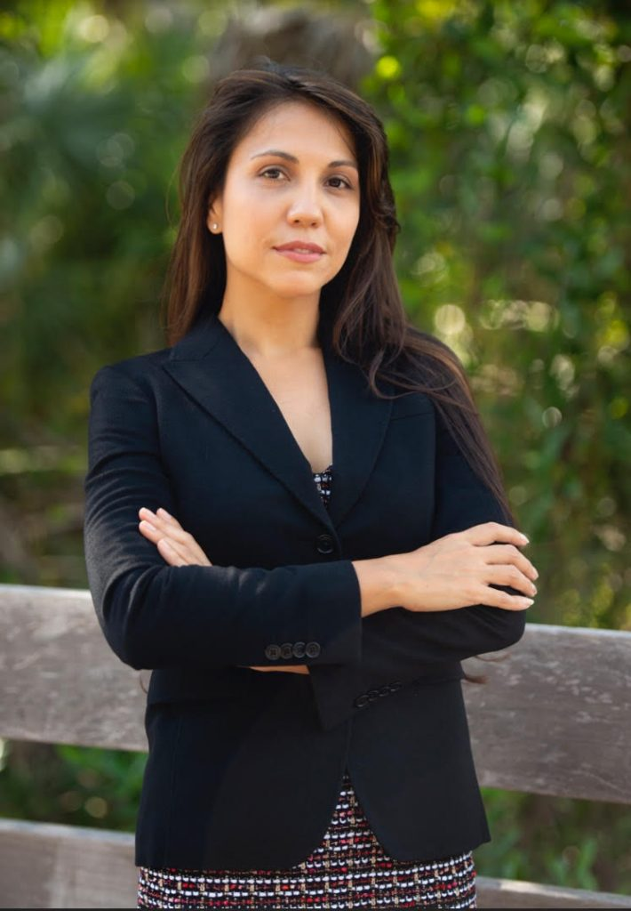 a woman with long dark hair wearing a black blazer over a dress crossing her arms