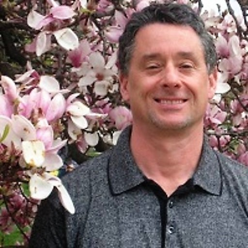 man wearing a gray shirt standing in front of a tree with pink and white flowers