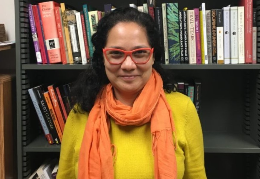 woman wearing red glasses and a bright yellow shirt with a coral scarf in front of a bookshelf