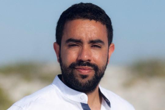 a headshot of a man with dark short hair and facial hair, wearing a white button up shirt