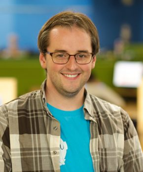 man with brown hair and glasses wearing blue shirt with flannel shirt over it